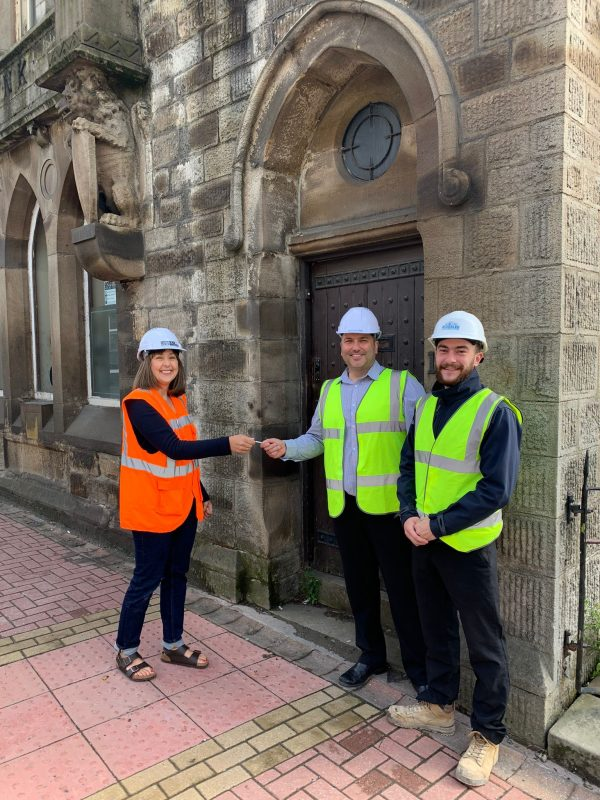 Valley Heritage hand over the keys to Rosslee Construction outside the front door of Alliance at the Lancashire and Yorkshire Bank